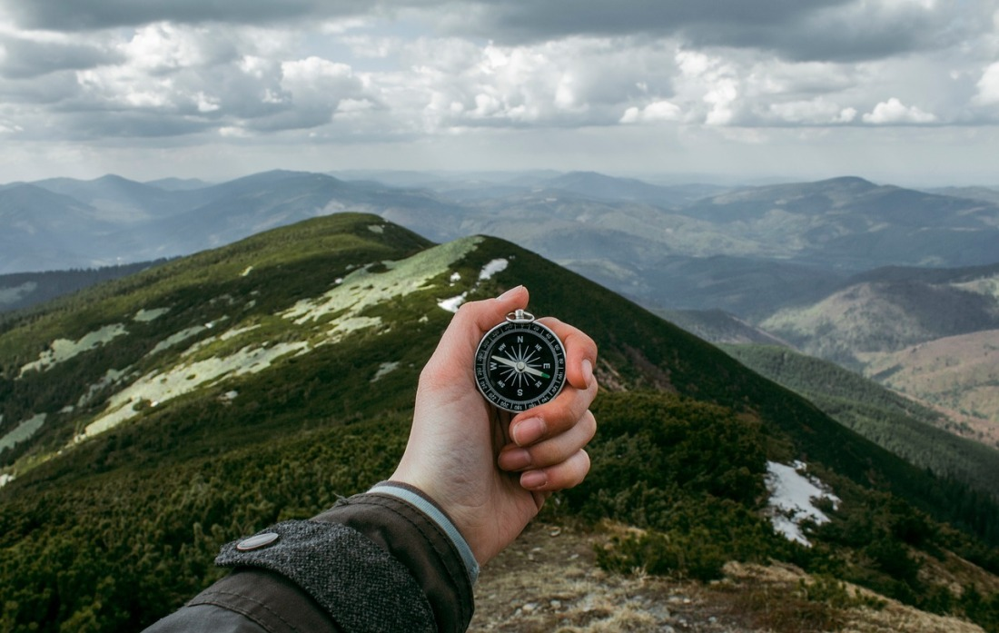 Man's hand holding out a compass on top of a hill, looking at a mountainous range in the background.